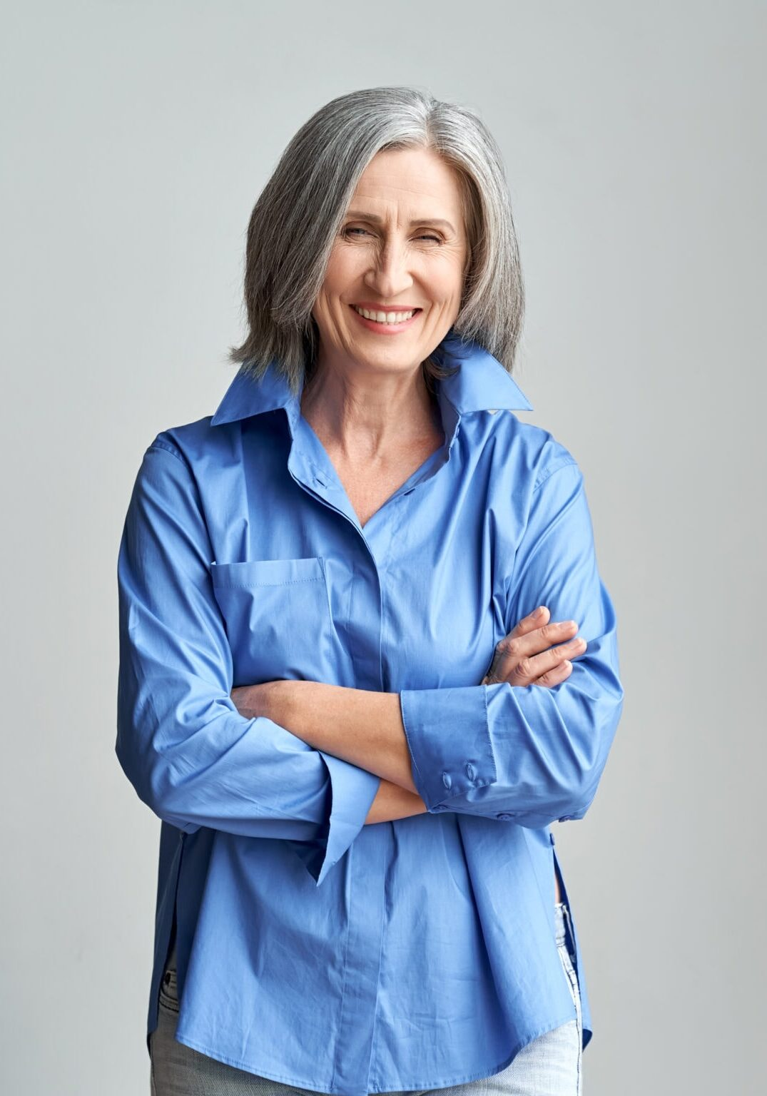Smiling elegant mature grey-haired woman standing with arms crossed isolated on grey wall background at home office. Happy middle aged old lady professional businesswoman, portrait.